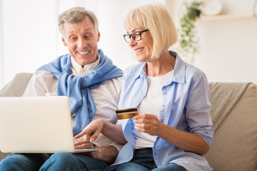 E-Commerce. Mature couple using laptop and credit card